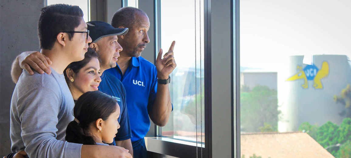 Vice Chancellor Parham shares the beautiful view of campus from the Mesa Court Towers with a new Anteater family during housing move in.