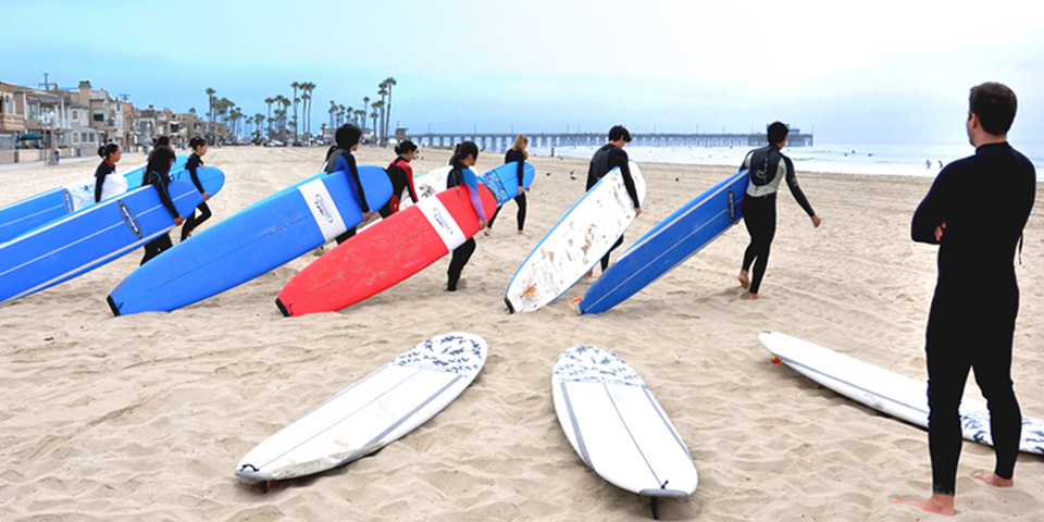 Students with surfboards on the beach