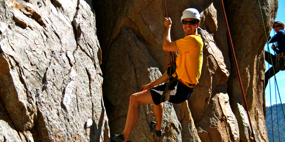 Young man rock climbing out doors assisted by rope